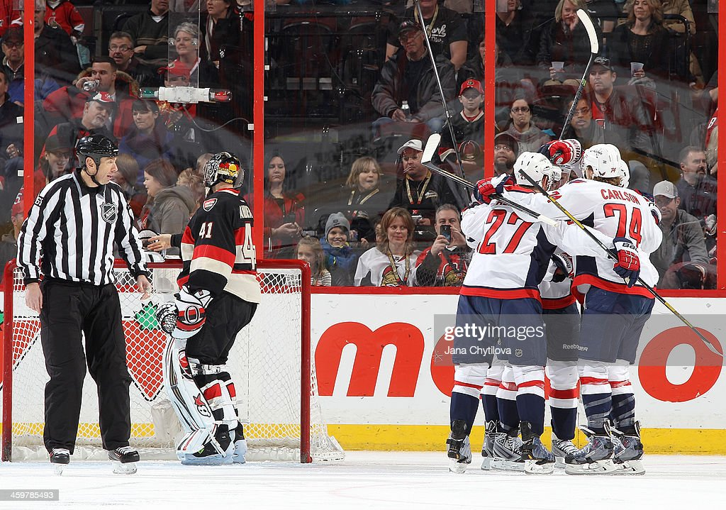 Karl Alzner #27 and John Carlson #74 of the Washington Capitals celebrate a first-period goal as Craig Anderson #41 of the Ottawa Senators looks on during an NHL game at Canadian Tire Centre on December 30, 2013 in Ottawa, Ontario, Canada.