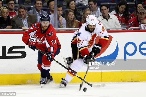 Karl Alzner of the Washington Capitals and Deryk Engelland of the Calgary Flames go after the puck in the third period at Verizon Center on March 21...