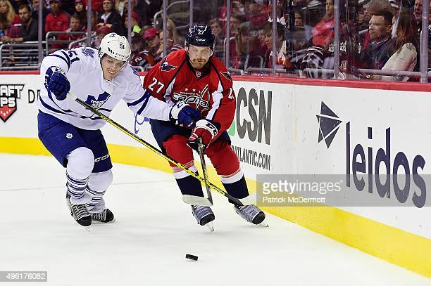 Karl Alzner of the Washington Capitals and Jake Gardiner of the Toronto Maple Leafs battle for the puck behind the net in the first period during an...