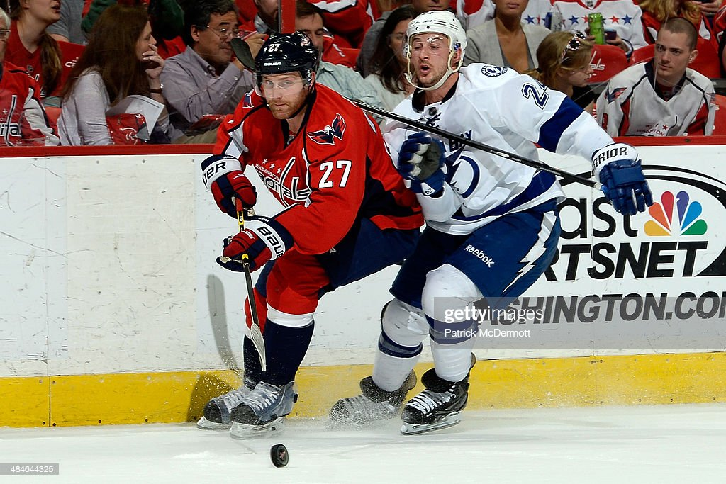 Karl Alzner #27 of the Washington Capitals and Ryan Callahan #24 of the Tampa Bay Lightning battle for the puck during the first period of an NHL game at Verizon Center on April 13, 2014 in Washington, DC.