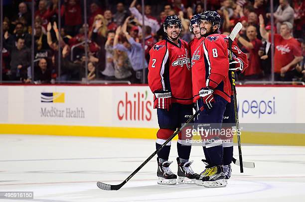 Karl Alzner of the Washington Capitals celebrates with Alex Ovechkin and Matt Niskanen after scoring an empty net goal against the Boston Bruins in...
