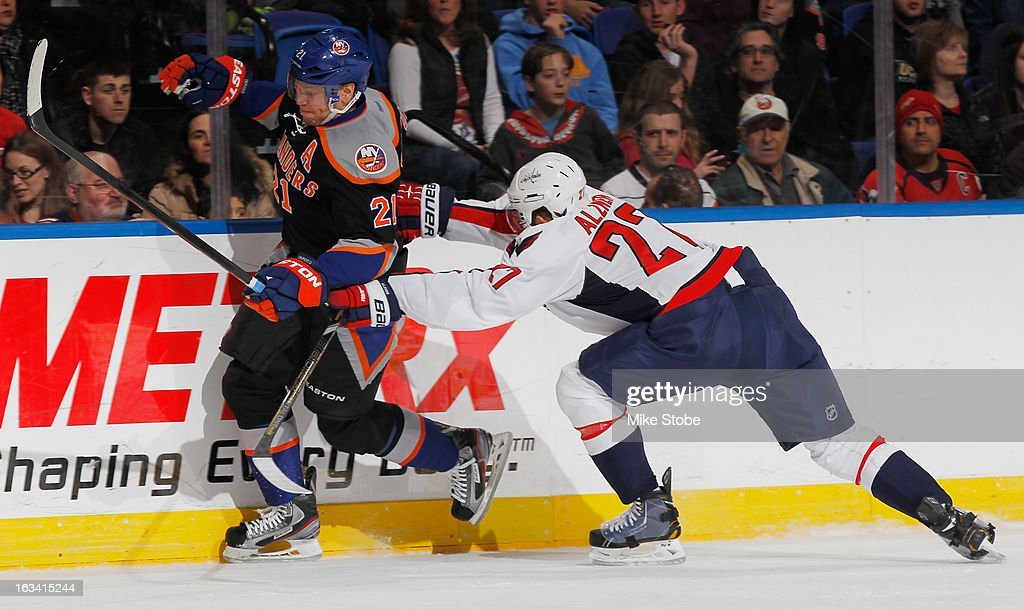 Karl Alzner #27 of the Washington Capitals checks Kyle Okposo #21 of the New York Islanders into the boards at Nassau Veterans Memorial Coliseum on March 9, 2013 in Uniondale, New York.