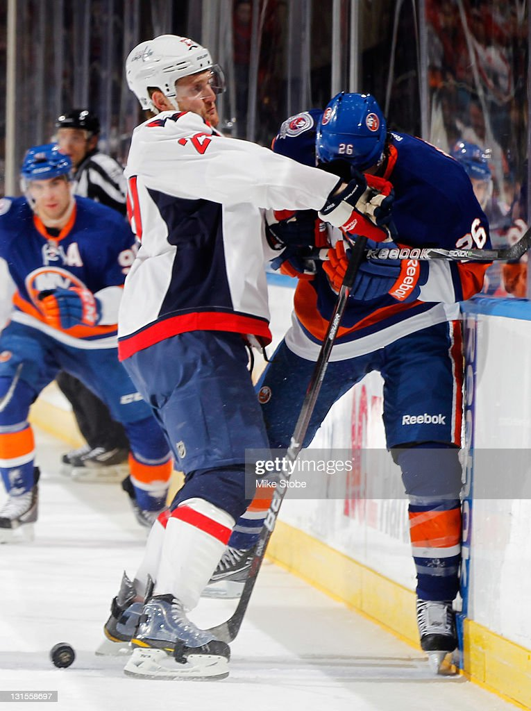 <a gi-track='captionPersonalityLinkClicked' href=/galleries/search?phrase=Karl+Alzner&family=editorial&specificpeople=3938829 ng-click='$event.stopPropagation()'>Karl Alzner</a> #27 of the Washington Capitals checks <a gi-track='captionPersonalityLinkClicked' href=/galleries/search?phrase=Matt+Moulson&family=editorial&specificpeople=3365493 ng-click='$event.stopPropagation()'>Matt Moulson</a> #26 of the New York Islanders hard into the boards at Nassau Veterans Memorial Coliseum on November 5, 2011 in Uniondale, New York.