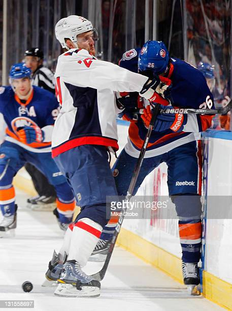 Karl Alzner of the Washington Capitals checks Matt Moulson of the New York Islanders hard into the boards at Nassau Veterans Memorial Coliseum on...