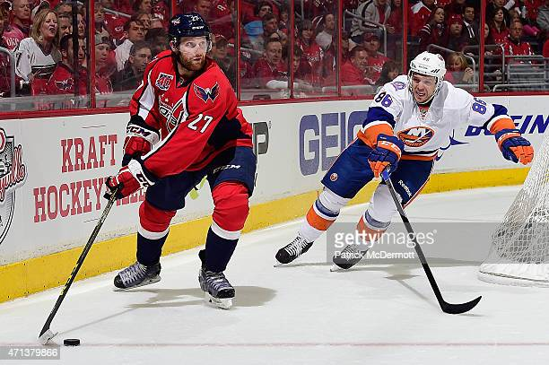 Karl Alzner of the Washington Capitals controls the puck against Nikolay Kulemin of the New York Islanders during the first period in Game Seven of...