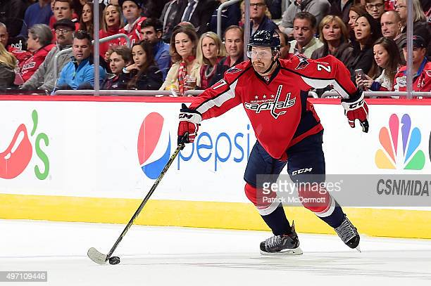 Karl Alzner of the Washington Capitals controls the puck against the Calgary Flames in the first period during an NHL game at Verizon Center on...
