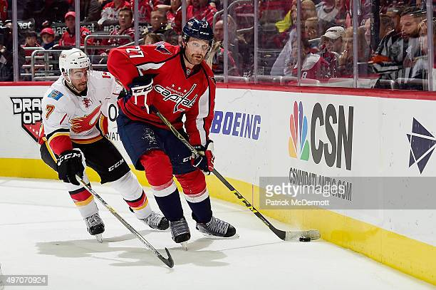 Karl Alzner of the Washington Capitals controls the puck behind the net against TJ Brodie of the Calgary Flames in the third period during an NHL...