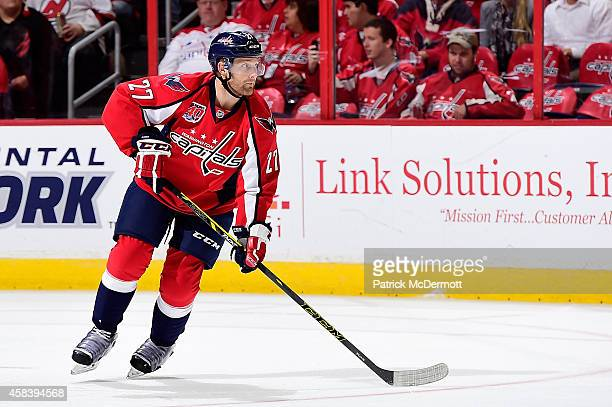 Karl Alzner of the Washington Capitals controls the puck in the third period during an NHL game against the New Jersey Devils at Verizon Center on...