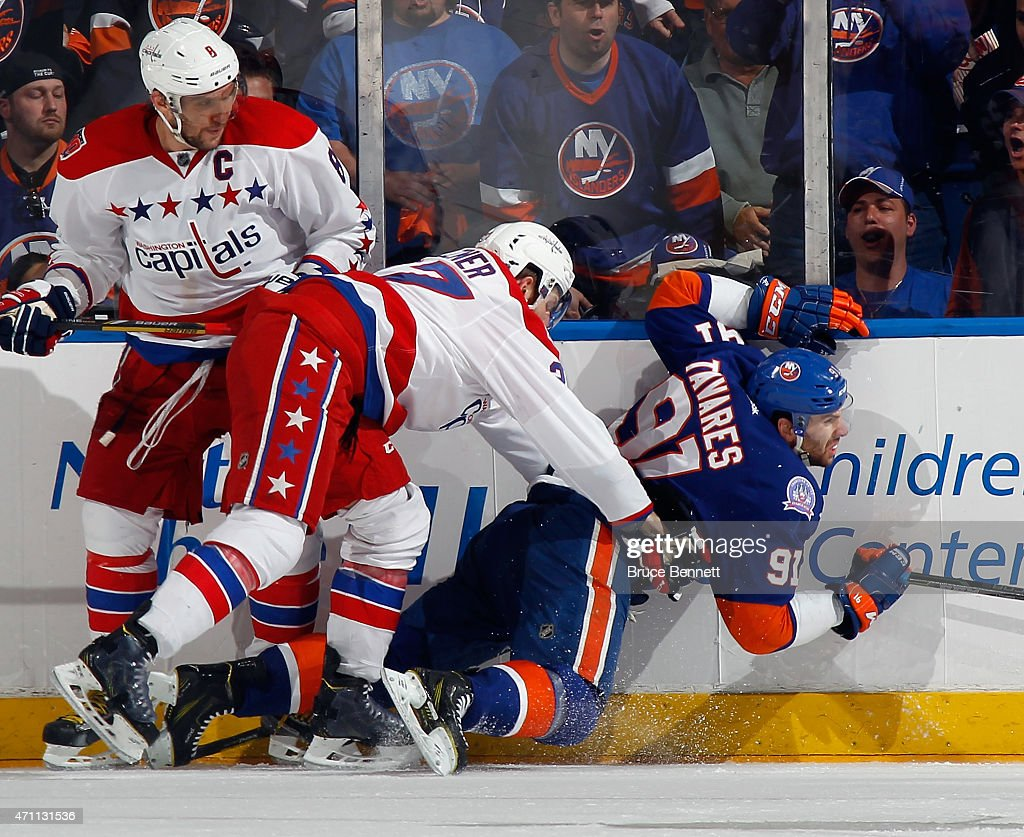 <a gi-track='captionPersonalityLinkClicked' href=/galleries/search?phrase=Karl+Alzner&family=editorial&specificpeople=3938829 ng-click='$event.stopPropagation()'>Karl Alzner</a> #27 of the Washington Capitals hits <a gi-track='captionPersonalityLinkClicked' href=/galleries/search?phrase=John+Tavares&family=editorial&specificpeople=601791 ng-click='$event.stopPropagation()'>John Tavares</a> #91 of the New York Islanders into the boards during the third period in Game Six of the Eastern Conference Quarterfinals during the 2015 NHL Stanley Cup Playoffs at the Nassau Veterans Memorial Coliseum on April 25, 2015 in Uniondale, New York. The Islanders defeated the Capitals 3-1.