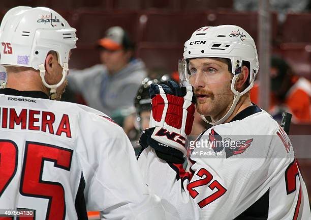 Karl Alzner of the Washington Capitals speaks with teammate Jason Chimera during a stoppage in play against the Philadelphia Flyers on November 12...