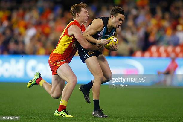 Karl Amon of the Power is tackled by Jesse Joyce of the Suns during the round 23 AFL match between the Gold Coast Suns and the Port Adelaide Power at...