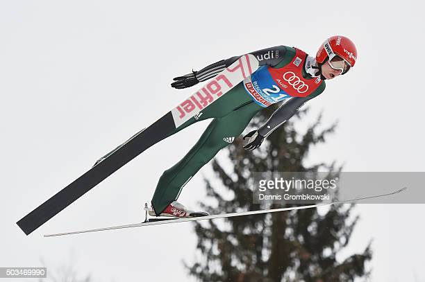 Karl Geiger of Germany soars through the air during his trial jump on Day 1 of the Bischofshofen 64th Four Hills Tournament ski jumping event on...