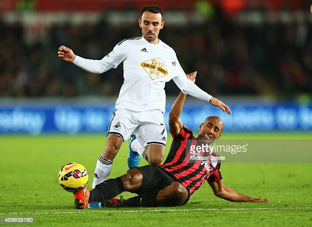 Karl Henry of QPR tackles Leon Britton of Swansea City during the Barclays Premier League match between Swansea City and Queens Park Rangers at...
