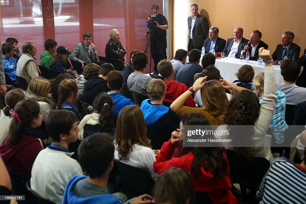 Karl Hopfner (L), CFO of Bayern Muenchen, Uli Hoeness (C), President of Bayern Muenchen and Karl-Heinz Rummenigge (R), CEO of Bayern Muenchen (all on the podium) talks to students at the German School Valencia on November 20, 2012 in Valencia, Spain.