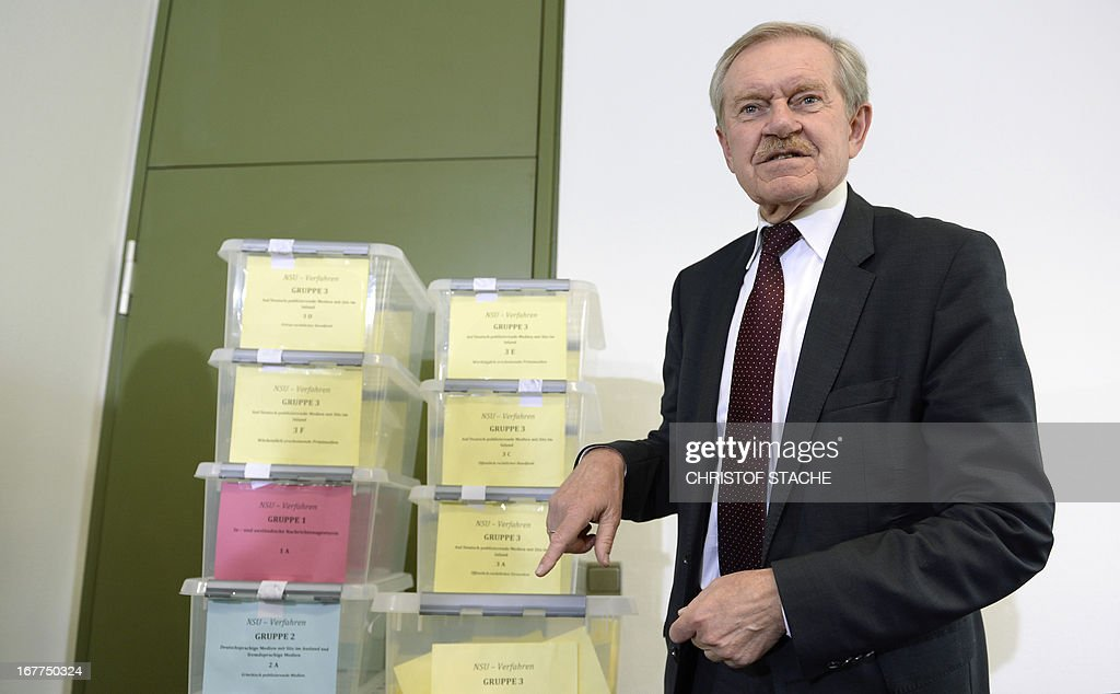 Karl Huber, President of the Higher Regional Court Munich (Oberlandesgerichtes Muenchen), points to boxes filled with media demands during a press conference on April 29, 2013 in Munich, southern Germany, after the lottery for the reserved press seats for the trial against the sole survivor of the far-right militants NSU and four other alleged neo-Nazi accomplices, to take place on May 6, 2013.