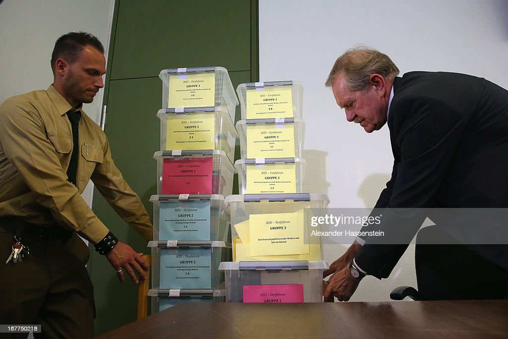 Karl Huber, President of the Oberlandgericht Muenchen court carries with a police officer the lottery boxes after a press conference following the lottery draw for the 50 media spots inside the courtroom for the upcoming NSU murder trial on April 29, 2013 in Munich, Germany. This the second accreditation process for the trial, which manay analysts are dubbing the trial of the decade and is scheduled to begin May 6, after lawsuits filed by Turkish media were upheld and the Munich court responded by redoing all accreditations. Eight of the ten victims of the NSU neo-Nazi murder trio were Turkish and one was Greek, and Turkish and Greek media are now guaranteed a small portion of the 50 seats reserved for media after no foreign media were given seats in the first accreditation process.