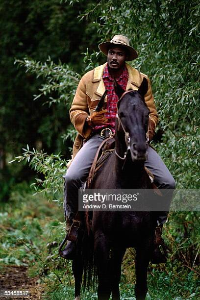 Karl Malone of the Utah Jazz rides a horse during the shooting of a film in Utah circa 1988 NOTE TO USER User expressly acknowledges and agrees that...
