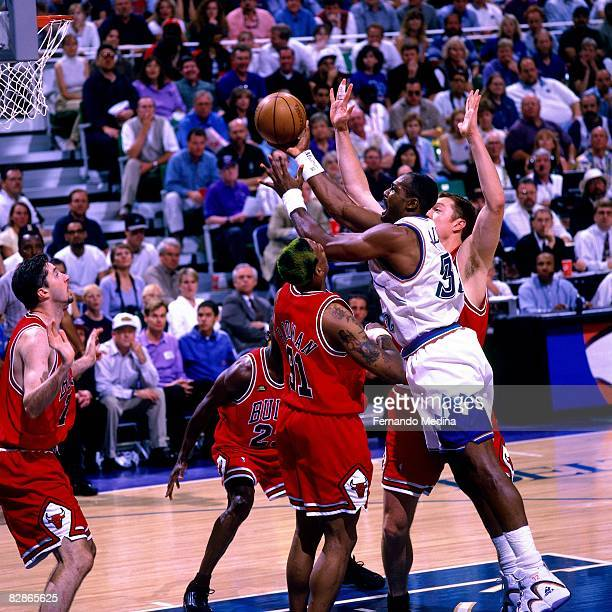 Karl Malone of the Utah Jazz shoots a layup against Dennis Rodman of the Chicago Bulls during Game Six of the 1998 NBA Finals played June 14 1998 at...