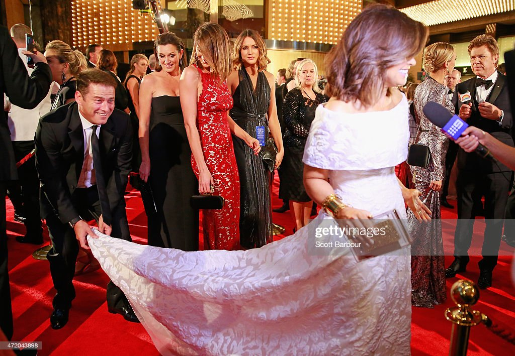 Karl Stefanovic bends down to adjust the dress of Lisa Wilkinson as Jesinta Campbell looks on at the 57th Annual Logie Awards at Crown Palladium on May 3, 2015 in Melbourne, Australia.