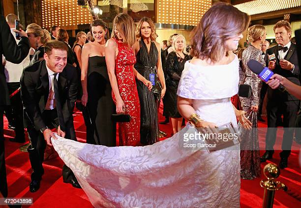Karl Stefanovic bends down to adjust the dress of Lisa Wilkinson as Jesinta Campbell looks on at the 57th Annual Logie Awards at Crown Palladium on...