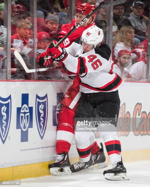 Karl Stollery of the New Jersey Devils checks Anthony Mantha of the Detroit Red Wings into the boards during an NHL game at Joe Louis Arena on...