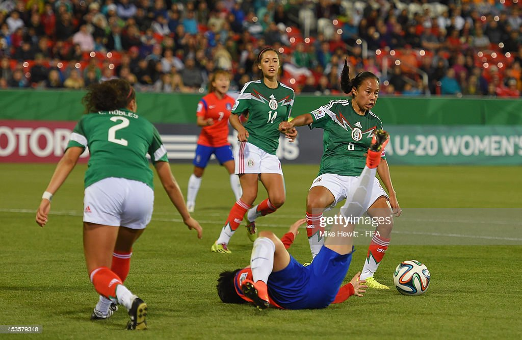 Karla Nieto of Mexico fouls Lee Geummin of Korea Republic to concede a penalty during the FIFA U-20 Women's World Cup Canada 2014 Group D match between Korea Republic and Mexico at the National Soccer Stadium on August 13, 2014 in Toronto, Canada.