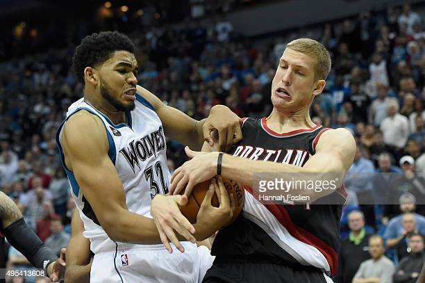 KarlAnthony Towns of the Minnesota Timberwolves and Mason Plumlee of the Portland Trail Blazers struggle over a jump ball in the fourth quarter of...