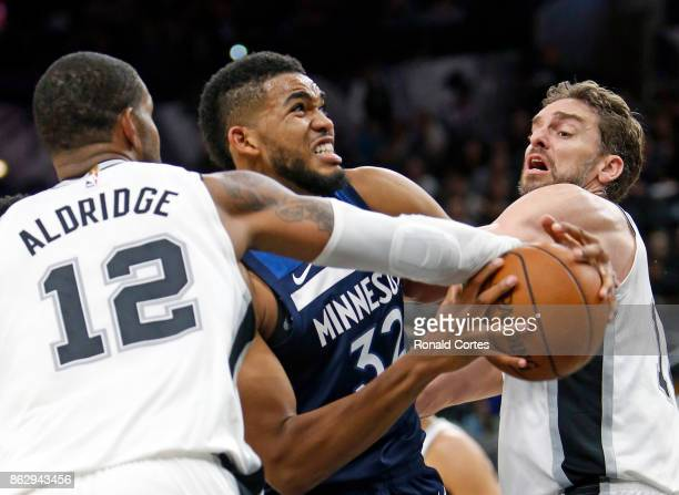 KarlAnthony Towns of the Minnesota Timberwolves drives between LaMarcus Aldridge of the San Antonio Spurs and Pau Gasol of the San Antonio Spurs at...