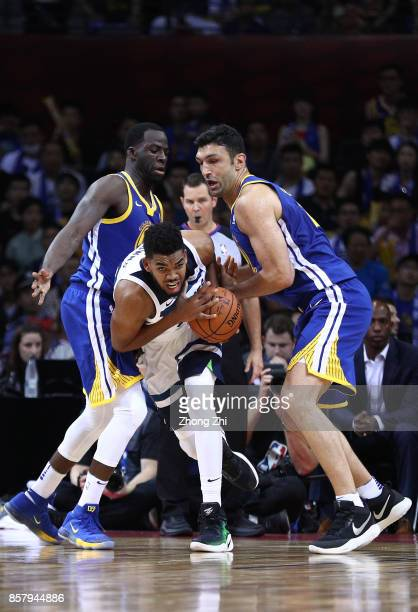 KarlAnthony Towns of the Minnesota Timberwolves in action against Zaza Pachulia and Draymond Green of the Golden State Warriors during the game...