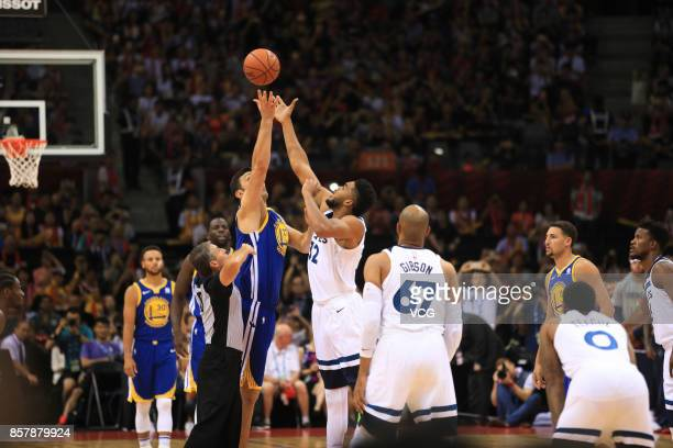 KarlAnthony Towns of the Minnesota Timberwolves jumps the opening tip against Zaza Pachulia of the Golden State Warriors during the game between the...