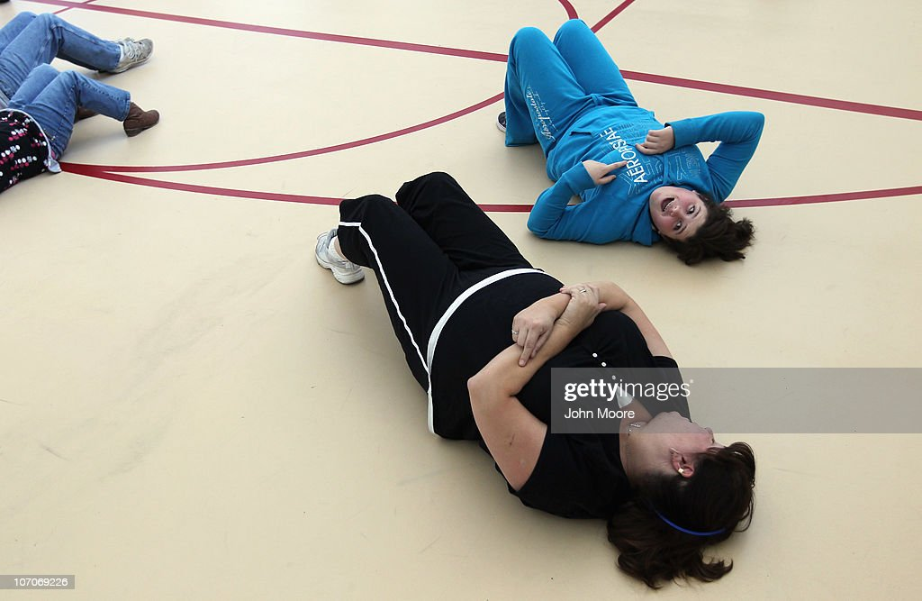 Karley Workman (R),14, and her mother Patricia Gould try to do situps during the Shapedown program for overweight adolescents and children on November 13, 2010 in Aurora, Colorado. The 10-week family-centered program held by the Denver area Children's Hospital teaches youth and their parents ways to lead a healthier more active lifestyle, as a longer lasting weight-loss alternative to dieting. Nationally, some 15 percent of children are overweight or obese, as are some 60 percent of adults.