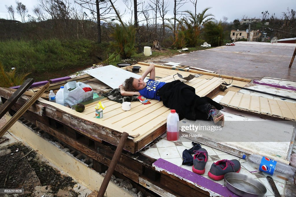 Karlian Mercado, 7, rests on the rubble that remains of her family's home after it was blown away by Hurricane Maria as it passed through the area on September 24, 2017 in Hayales de Coamo, Puerto Rico. Puerto Rico experienced widespread damage after Hurricane Maria, a category 4 hurricane, passed through.