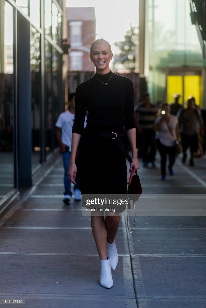 Karlie Kloss wearing black longshirt, black skirt, white heels, red bag seen in the streets of Manhattan outside Diane von Furstenberg during New York Fashion Week on September 10, 2017 in New York City.