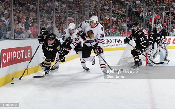 Karlis Skrastins of the Dallas Stars tries to keep the puck away against Fernando Pisani and Michael Frolik of the Chicago Blackhawks at the American...