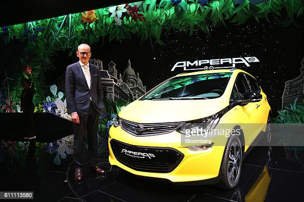 KarlThomas Neumann chief executive officer of Adam Opel AG poses for a photograph beside a Opel Ampera electric automobile ahead of an interview on...