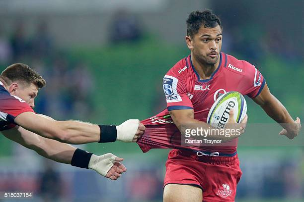 Karmichael Hunt of the Reds evades a tackle from Adam Thomson of the Rebels during the round three Super Rugby match between the Rebels and the Reds...