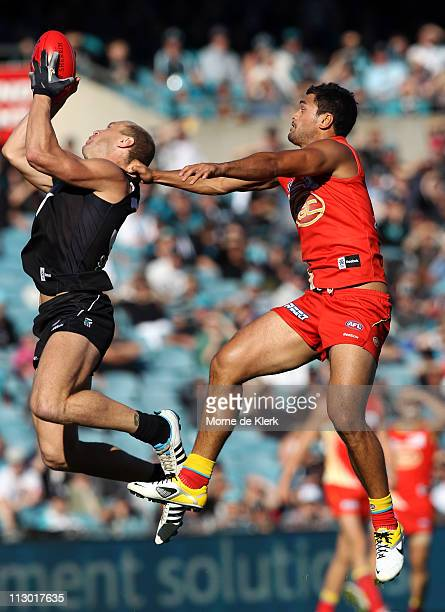 Karmichael Hunt of the Suns and Chad Cornes of the Power compete in the air during the round five AFL match between the Port Adelaide Power and the...