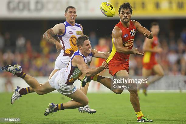 Karmichael Hunt of the Suns handballs while tackled by James Polkinghorne of the Lions during the round three AFL match between the Gold Coast Suns...