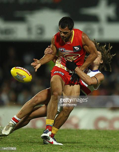 Karmichael Hunt of the Suns is tackled by Luke Dahlhaus of the Bulldogs during the round eight AFL match between the Western Bulldogs and the Gold...