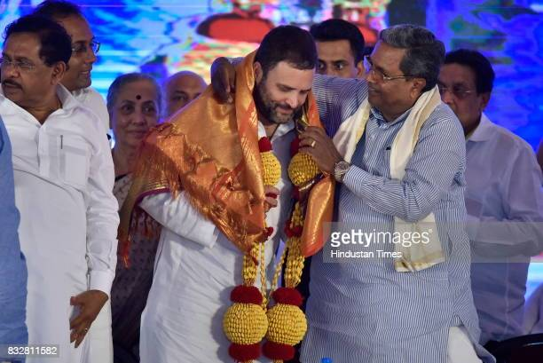 Karnataka Chief Minister Siddaramaiah felicitates Congress Vice President Rahul Gandhi during a public meeting at National College ground on August...