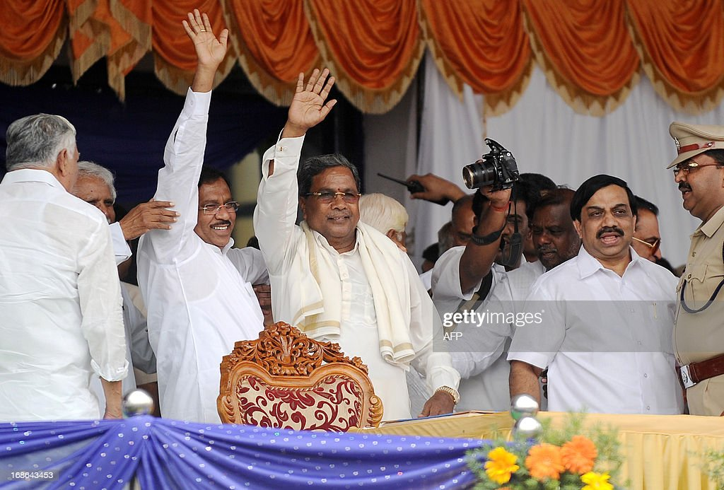 Karnataka Pradesh Congress Committee (KPCC) chief, Siddaramaiah (C), along with KPCC president G. Parameshwar (R), waves to the crowd during his swearing-in ceremony as Karnataka chief minister, in Bangalore on May 13, 2013. Congress leader Siddaramaiah takes over as 22nd Karnataka chief minister after leading his party to a huge win in last week's assembly elections, winning 121 seats in the 224-seat assembly. AFP PHOTO/Manjunath KIRAN