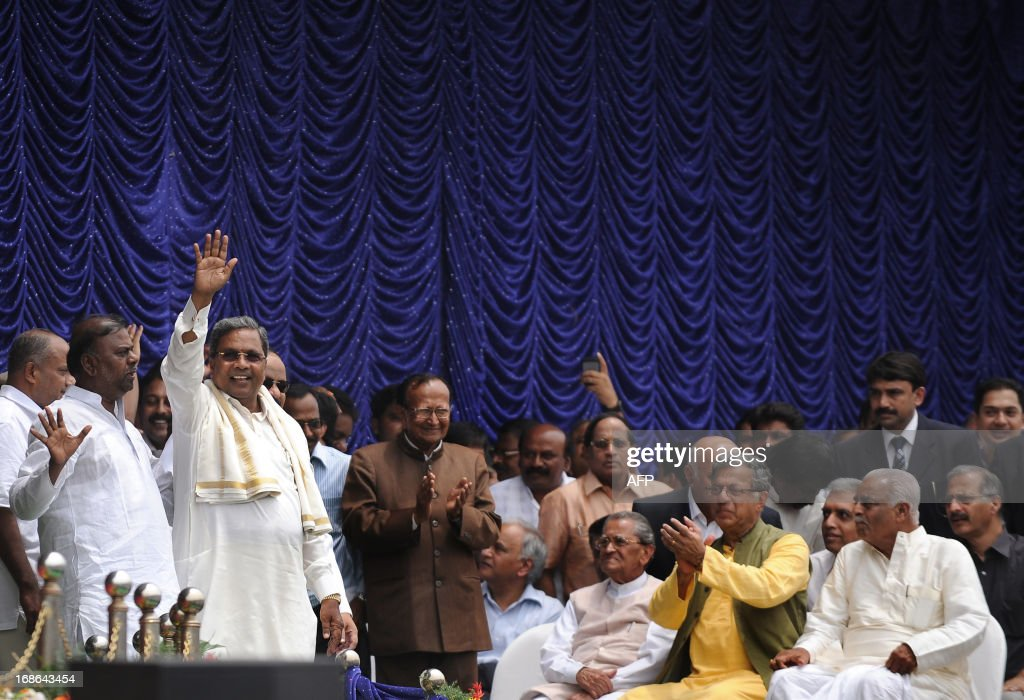 Karnataka Pradesh Congress Committee (KPCC) chief, Siddaramaiah (2L) waves to the crowd during his swearing-in ceremony as Karnataka chief minister, in Bangalore on May 13, 2013. Congress leader Siddaramaiah takes over as 22nd Karnataka chief minister after leading his party to a huge win in last week's assembly elections, winning 121 seats in the 224-seat assembly. AFP PHOTO/Manjunath KIRAN