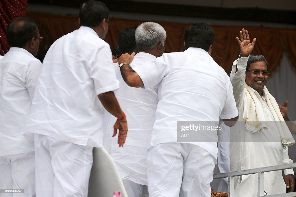 Karnataka Pradesh Congress Committee (KPCC) chief, Siddaramaiah (R) waves to the crowd during his swearing-in ceremony as Karnataka chief minister, in Bangalore on May 13, 2013. Congress leader Siddaramaiah takes over as 22nd Karnataka chief minister after leading his party to a huge win in last week's assembly elections, winning 121 seats in the 224-seat assembly. AFP PHOTO/Manjunath KIRAN