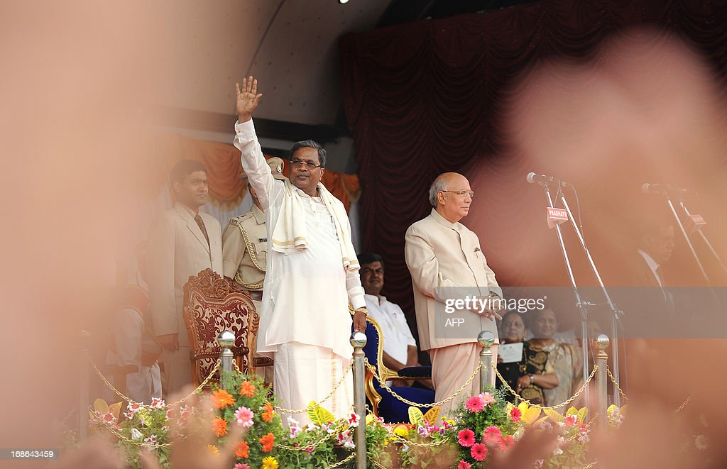 Karnataka Pradesh Congress Committee (KPCC) chief, Siddaramaiah (L) waves to the crowd as Karnataka Governor HR Bhardwaj looks on during his swearing-in ceremony as Karnataka chief minister, in Bangalore on May 13, 2013. Congress leader Siddaramaiah takes over as 22nd Karnataka chief minister after leading his party to a huge win in last week's assembly elections, winning 121 seats in the 224-seat assembly. AFP PHOTO/Manjunath KIRAN
