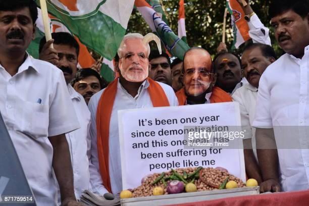 Karnataka Pradesh Congress Committee member sports a caricatured mask of the prime minister of India Narendra Modi and Finance Minister Arun Jaitley...