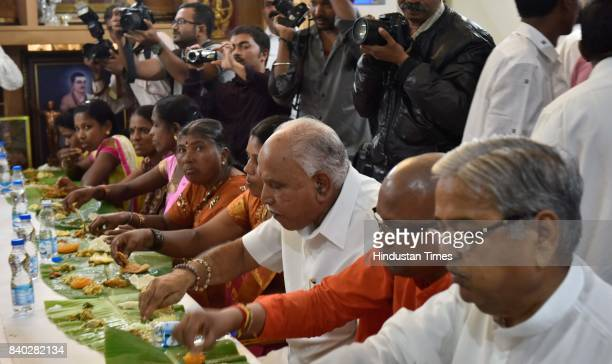 Karnataka state president BS Yeddyurappa having lunch with thirty three Dalit families at his residence along with Madara Chennaiah Swami on August...