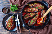 Karniyarik - Stuffed Eggplants, Aubergines with ground beef and vegetables baked with tomato sauce served on a plate with fork and knife, turkish cuisine, horizontal view from above, close-up, flatlay