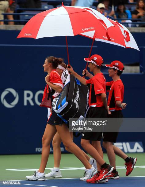 Karolina Pliskova of Czech Republic and Caroline Wozniacki of Denmark leave Centre Court as the start of their match is delayed due to rain during...