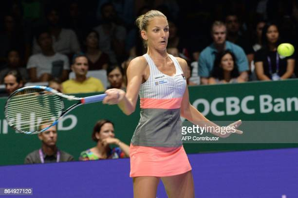 Karolina Pliskova of the Czech Republic hits a return against Venus Williams of the US during the WTA Finals tennis tournament in Singapore on...