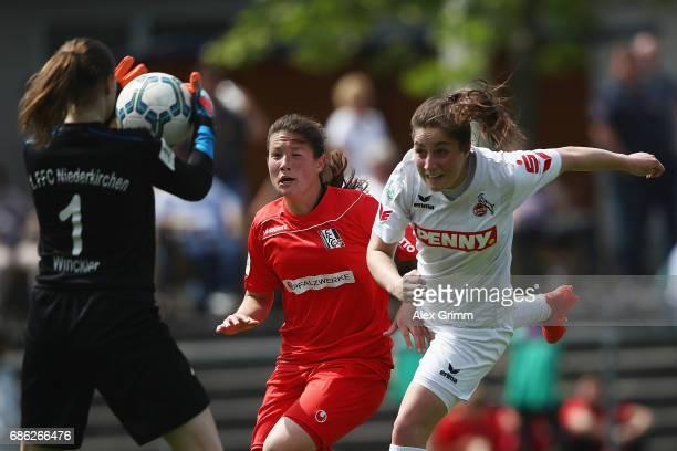 Karoline Kohr of Koeln tries to score with header against Ann Katrin Striekert and goalkeeper Nadine Winkler of Niederkirchen during the Second...
